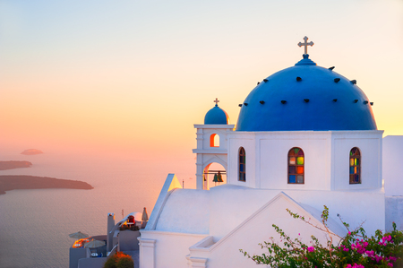 Church with blue dome at sunset on Santorini island, Greece. Summer landscape, sea view