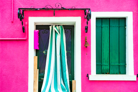 Window with green shutters and door on the pink wall. Colorful architecture in Burano island, Venice, Italy. Stock Photo