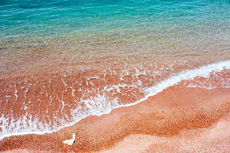Beautiful sea beach with red sand and turquoise water. Adriatic sea, Montenegro. Summer travel background, top view