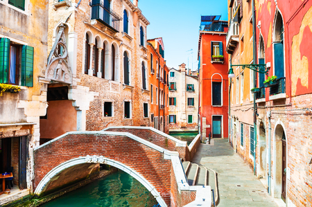 Scenic canal with bridge and colorful architecture in Venice, Italy. Famous travel destination