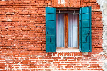 Window with blue shutters on the old red brick wall. Burano island, Venice, Italy. Stock Photo