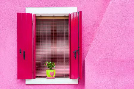 Window with pink shutters on the pink wall. Colorful architecture in Burano island, Venice, Italy.