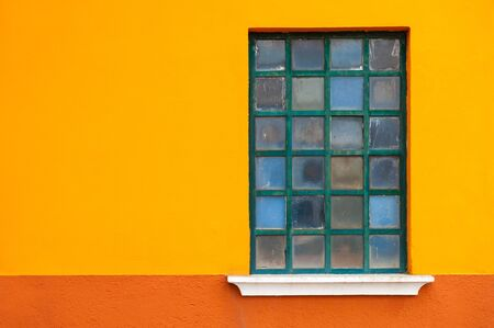 Window on the orange wall of the house. Colorful architecture in Burano island, Venice, Italy. Stock Photo