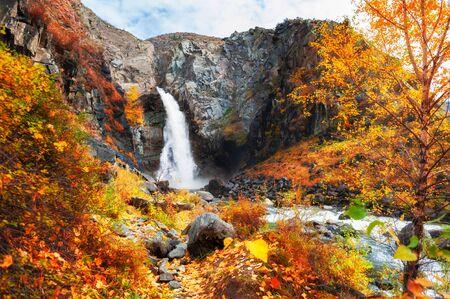 Kurkure waterfall with yellow autumn trees in Altai mountains, Siberia, Russia. Beautiful autumn landscape Stock Photo