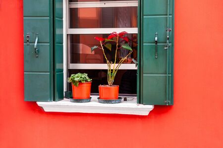 Window with green shutters on the red wall. Colorful architecture in Burano island, Venice, Italy. Stock Photo