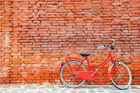 Bicicletta rossa vicino al vecchio muro di mattoni rossi. Venezia, Italia