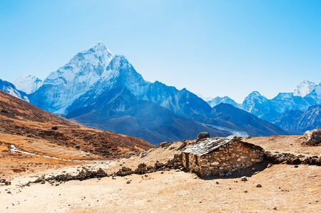 Stone house in the mountains and view of Mount Ama Dablam in Himalayas, Nepal. Khumbu valley, Everest region