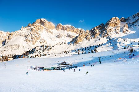 Ski slopes on ski resort in winter Dolomite Alps. Val Di Fassa, Italy. Winter holidays, travel destination