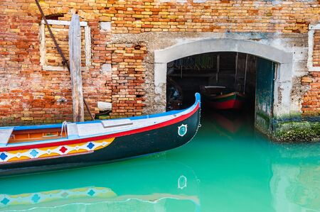 Old venetian gondola on the canal in Venice, Italy. Garage for boats on the canal Imagens