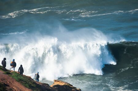 People watching big waves in Nazare, Portugal. Season of big waves lasts here from November to March