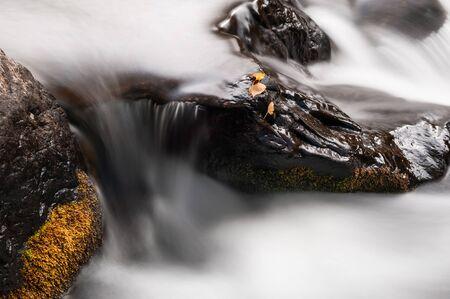 Flowing water between rocks in mountain river. Long exposure shoot. Beautiful autumn landscape