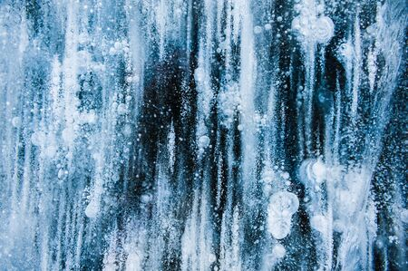 Blue ice with air bubbles in the frozen lake. Macro image. Winter nature background Banque d'images