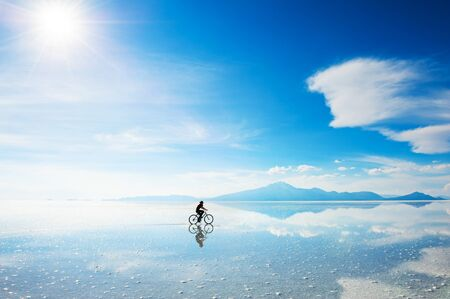 Woman riding a bicycle on the Salar de Uyuni salt flat in Bolivia. South America landscapes