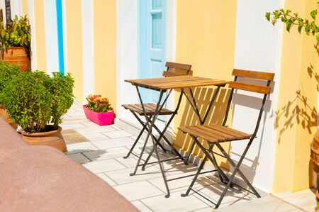 Two wooden chairs with table on the street. Traditional greek architecture on Santorini island, Greece.