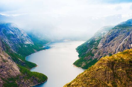 Lake in the mountains in foggy morning, Norway. Ringedalsvatnet lake on the hiking trek to Trolltunga. Summer landscape 免版税图像