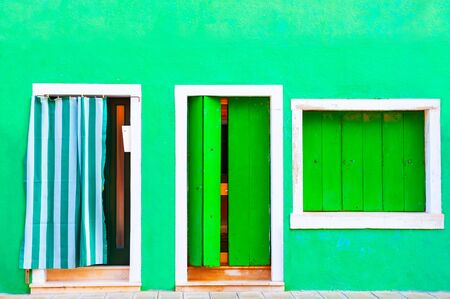 Window and door with green shutters on the green painted facade of the house. Colorful architecture in Burano island, Venice, Italy. Stok Fotoğraf