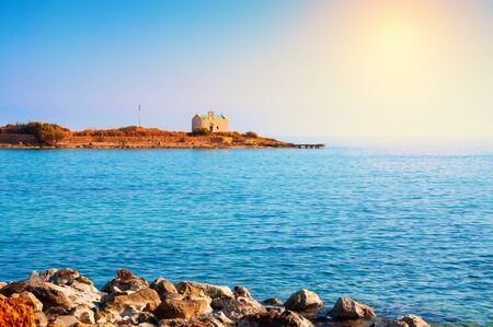 Small island with chapel near the coast on Crete island, Greece. Summer landscape