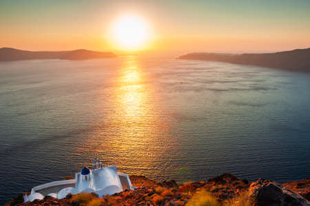 Small church on the cliffs at sunset. Santorini island, Greece. Beautiful summer landscape. Famous travel destination