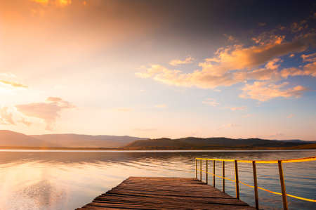 Old wooden pier on the lake at sunset. Beautiful autumn landscape. South Ural, Bashkortostan, Russia