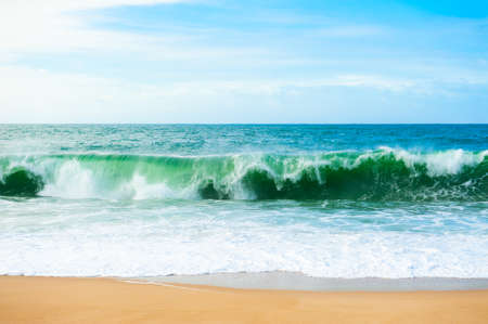 Waves on the coast of Atlantic ocean. Algarve, Portugal. Beautiful beach with white sand and turquoise water. Summer nature background.