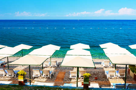 Pebble beach with umbrellas in Kemer, Turkey. Beautiful summer seascape. Travel destination concept