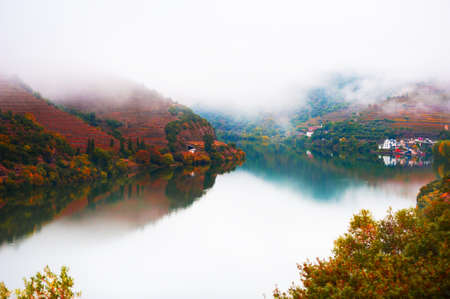 Douro river valley in Portugal. Misty morning, vineyards on the mountains and their reflections in the water. Portuguese wine region. Beautiful autumn landscape