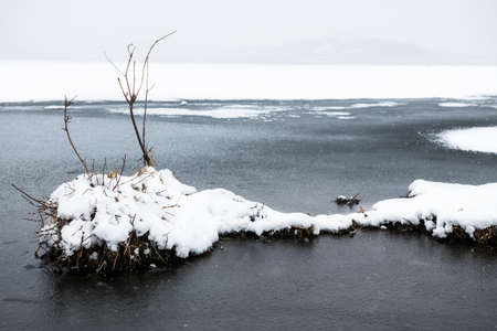 Ice with snow on the shore of lake during snowfall. Beautiful winter landscape