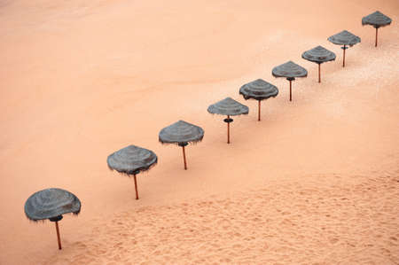 Sun umbrellas on the sandy beach. Top view. Beautiful coast of Atlantic ocean in Algarve, Portugal. Summer travel background. Reklamní fotografie