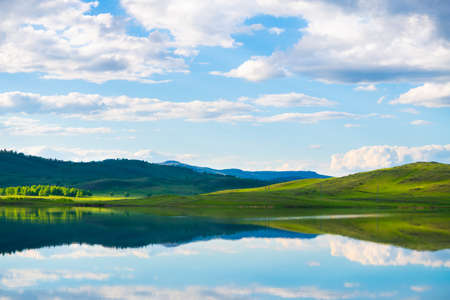 Green mountains and their reflections in the lake. Beautiful summer landscape. South Ural, Russia Reklamní fotografie