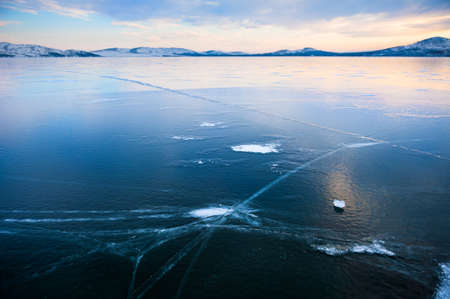 Ice on the frozen lake at sunset. Beautiful winter landscape. Bannoye lake in South Ural, Russia
