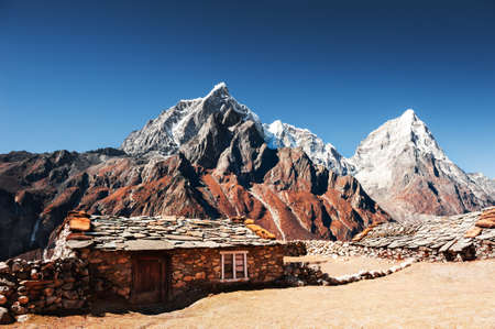 Traditional nepalese houses and view of Taboche and Cholatse peaks in Himalaya mountains. Khumbu valley, Everest region, Nepal.