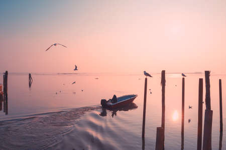 Boat sailing on the canal at sunrise in Burano island, Venice, Italy. Beautiful seascape, pink sky and soaring seagulls over the water