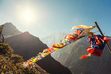 Buddhist prayer flags in Himalaya mountains at sunrise. View of Thamserku mount in Himalayas, Khumbu valley, Everest region, Nepal.