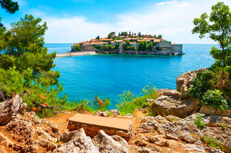 Sveti Stefan island in Montenegro. Luxury resort with beautiful beach at Adriatic sea. Bench with a view of the island. Famous travel destination