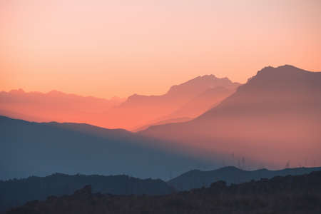 Mountain range in pink sunlight at sunset. Blue mountains with the pink sky. Beautiful autumn landscape, nature background. North Caucasus, Russia.