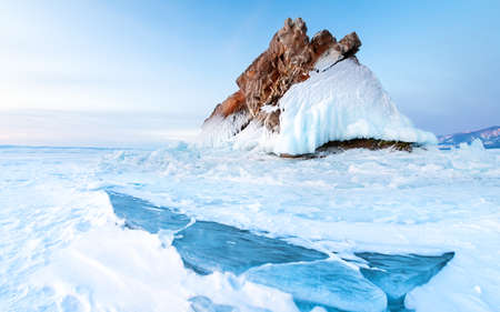 Rock on the frozen Baikal lake in winter. Snow and ice on the surface of the lake. Baikal, Siberia, Russia. Beautiful winter landscape at sunrise.