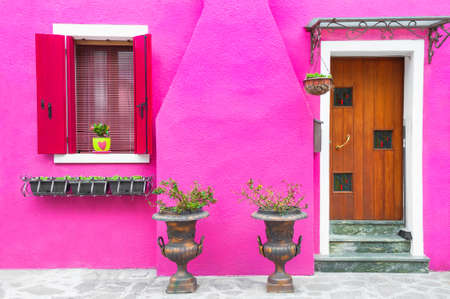 Door and windows with flowers on the pink facade of the house. Colorful architecture in Burano island, Venice, Italy. Zdjęcie Seryjne