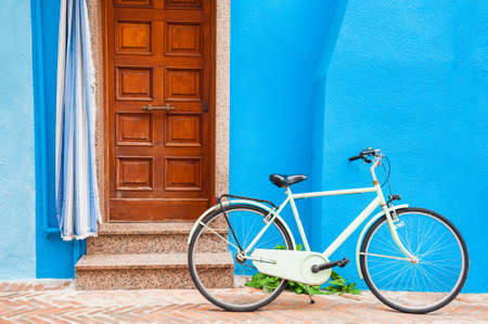 White bicycle near the door of the blue-painted house. Colorful architecture in Burano island, Venice, Italy. Zdjęcie Seryjne