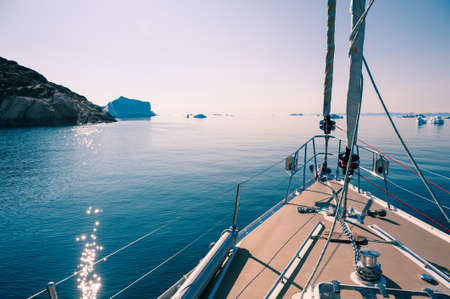 Yacht sailing among icebergs in Atlantic ocean in Greenland. Summer seascape