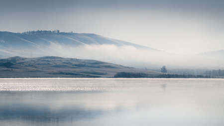 Beautiful lake in misty morning. Mountains reflected in the calm water surface. Autumn landscape. South Ural, Russia.