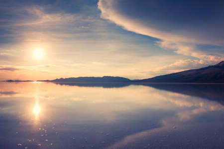 Mirror surface of Salar de Uyuni salt flat at sunset in Bolivia. Mountains and sky are reflected in the water surface. Famous travel destination