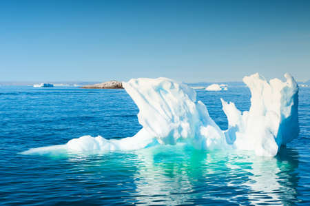 Iceberg in Atlantic ocean. Ilulissat icefjord, west coast of Greenland. Blue sea and the blue sky