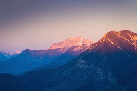Mountain range in pink sunlight at sunrise. Beautiful autumn landscape, nature background. North Caucasus, Russia. Stock fotó