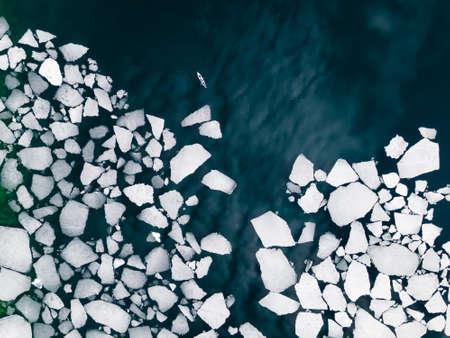 Kayak sailing between ice floes on Baikal lake in spring. Aerial drone view. Baikal lake, Siberia, Russia