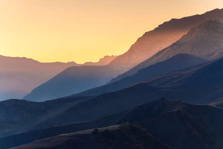 Mountain range at sunset. North Caucasus, Russia. Blue mountains and the pink sky. Beautiful autumn landscape