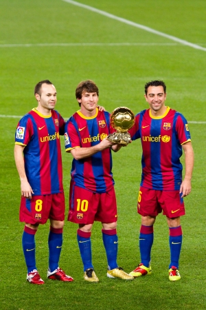 BARCELONA, SPAIN - JANUARY 12, 2011: Lionel Messi , Andres Iniesta and Xavi Hernandez shows the FIFA World Player Golden Ball Award to FC Barcelona soccer supporters in Camp Nou stadium. Stock Photo - 11366653