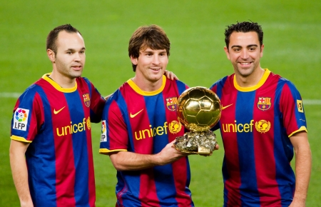 BARCELONA, SPAIN - JANUARY 12, 2011: Lionel Messi , Andres Iniesta and Xavi Hernandez shows the FIFA World Player Golden Ball Award to FC Barcelona soccer supporters in Camp Nou stadium.