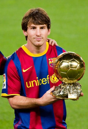 BARCELONA, SPAIN - JANUARY 12, 2011: Lionel Messi shows the FIFA World Player Golden Ball Award to FC Barcelona soccer supporters in Camp Nou stadium.