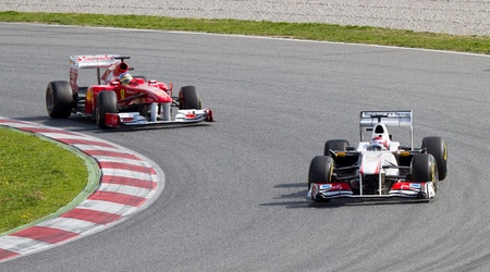 BARCELONA, SPAIN - FEBRUARY 18, 2011: Fernando Alonso of Ferrari and Kamui Kobayashi of Sauber team driving his F1 car during Formula One Teams Test Days at Catalunya circuit.