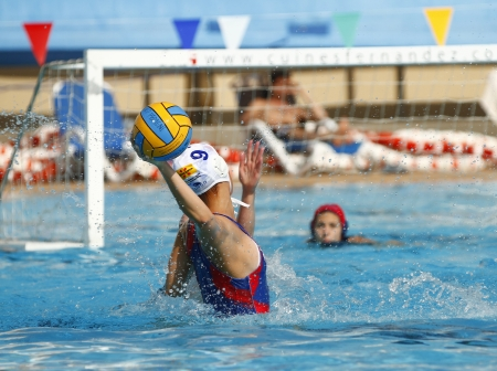 MATARO, SPAIN - APRIL 10, 2010: Unidentified water polo player in action during the women Spanish league match between CN Mataro and Sant Andreu, final score 4 - 7.
